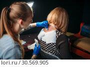 Купить «Tattoo artist prepares client skin for tattooing», фото № 30569905, снято 22 декабря 2017 г. (c) Tryapitsyn Sergiy / Фотобанк Лори