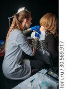 Female tattooer makes tattoo by machine. Стоковое фото, фотограф Tryapitsyn Sergiy / Фотобанк Лори