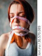 Купить «Womans face tied with measuring tape, weight loss», фото № 30570089, снято 10 января 2018 г. (c) Tryapitsyn Sergiy / Фотобанк Лори