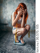 Купить «Thin woman in underwear weighed on a scale», фото № 30570105, снято 10 января 2018 г. (c) Tryapitsyn Sergiy / Фотобанк Лори