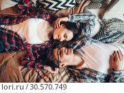 Купить «Love couple in clothes embrace on couch, top view», фото № 30570749, снято 17 февраля 2018 г. (c) Tryapitsyn Sergiy / Фотобанк Лори