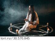 Купить «Woman holds burnt rose in hands, dark magic ritual», фото № 30570845, снято 27 февраля 2018 г. (c) Tryapitsyn Sergiy / Фотобанк Лори