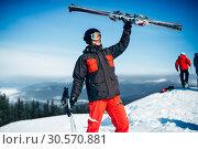 Купить «Skier holds skis and poles in hands», фото № 30570881, снято 6 марта 2018 г. (c) Tryapitsyn Sergiy / Фотобанк Лори
