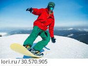 Купить «Snowboarder in glasses poses with board in hands», фото № 30570905, снято 6 марта 2018 г. (c) Tryapitsyn Sergiy / Фотобанк Лори