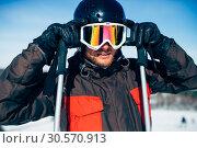 Купить «Male skier in helmet puts on glasses, front view», фото № 30570913, снято 6 марта 2018 г. (c) Tryapitsyn Sergiy / Фотобанк Лори
