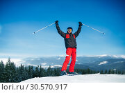 Male skier hands up on the top of mountain. Стоковое фото, фотограф Tryapitsyn Sergiy / Фотобанк Лори