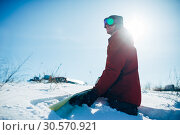 Купить «Snowboarder sitting on snowy slope in sunny day», фото № 30570921, снято 6 марта 2018 г. (c) Tryapitsyn Sergiy / Фотобанк Лори