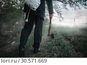 Slayer with an axe carries the victim's body. Стоковое фото, фотограф Tryapitsyn Sergiy / Фотобанк Лори