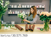 Купить «Female florist decorate fresh flower composition», фото № 30571769, снято 4 мая 2018 г. (c) Tryapitsyn Sergiy / Фотобанк Лори