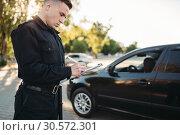 Купить «Male police officers writes a fine on the road», фото № 30572301, снято 6 июня 2018 г. (c) Tryapitsyn Sergiy / Фотобанк Лори