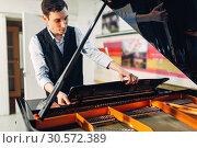 Купить «Male pianist opens the lid of black grand piano», фото № 30572389, снято 10 июня 2018 г. (c) Tryapitsyn Sergiy / Фотобанк Лори
