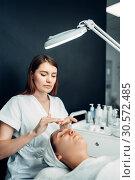 Купить «Beautician apply the cream mask to patient face», фото № 30572485, снято 13 июня 2018 г. (c) Tryapitsyn Sergiy / Фотобанк Лори