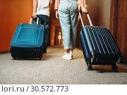 Купить «Couple with suitcase walking by the hotel corridor», фото № 30572773, снято 30 июня 2018 г. (c) Tryapitsyn Sergiy / Фотобанк Лори