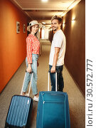 Smiling couple with suitcase in hotel hallway. Стоковое фото, фотограф Tryapitsyn Sergiy / Фотобанк Лори