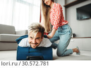 Купить «Cheerful girl packed her husband in a suitcase», фото № 30572781, снято 30 июня 2018 г. (c) Tryapitsyn Sergiy / Фотобанк Лори