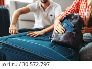 Couple packing their suitcases and take documents. Стоковое фото, фотограф Tryapitsyn Sergiy / Фотобанк Лори