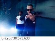 Bodyguard with a gun protect female VIP client. Стоковое фото, фотограф Tryapitsyn Sergiy / Фотобанк Лори