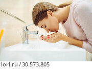 Woman washes her face at the sink in bathroom. Стоковое фото, фотограф Tryapitsyn Sergiy / Фотобанк Лори