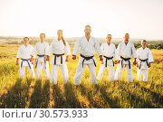 Купить «Karate group in white kimono, workout in field», фото № 30573933, снято 26 августа 2018 г. (c) Tryapitsyn Sergiy / Фотобанк Лори