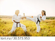 Купить «Two female karate in kimono fight in summer field», фото № 30573953, снято 26 августа 2018 г. (c) Tryapitsyn Sergiy / Фотобанк Лори