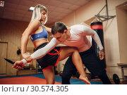 Купить «Female person practicing knee kick to the stomach», фото № 30574305, снято 9 сентября 2018 г. (c) Tryapitsyn Sergiy / Фотобанк Лори