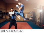 Male kickboxer doing kick in jump, kickboxing. Стоковое фото, фотограф Tryapitsyn Sergiy / Фотобанк Лори