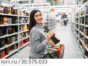 Woman with bottle of alcoholic beverage in shop. Стоковое фото, фотограф Tryapitsyn Sergiy / Фотобанк Лори