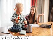 Купить «Mother works, kid helps her, motherhood problems», фото № 30575177, снято 4 ноября 2018 г. (c) Tryapitsyn Sergiy / Фотобанк Лори