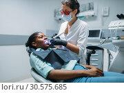 Купить «Dentist installs the seal on tooth, dental clinic», фото № 30575685, снято 1 декабря 2018 г. (c) Tryapitsyn Sergiy / Фотобанк Лори