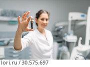 Купить «Dentist shows tooth pin and model, dental clinic», фото № 30575697, снято 1 декабря 2018 г. (c) Tryapitsyn Sergiy / Фотобанк Лори