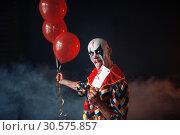 Купить «Spooky bloody clown with knife holds air balloons», фото № 30575857, снято 7 декабря 2018 г. (c) Tryapitsyn Sergiy / Фотобанк Лори