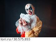 Купить «Bloody clown with crazy eyes holds fan of money», фото № 30575893, снято 7 декабря 2018 г. (c) Tryapitsyn Sergiy / Фотобанк Лори