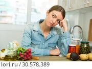 Купить «Tired woman sitting at home kitchen», фото № 30578389, снято 21 мая 2019 г. (c) Яков Филимонов / Фотобанк Лори