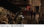 Купить «Lively street with outdoor cafe in night Venice, Italy», видеоролик № 30579853, снято 22 апреля 2018 г. (c) Данил Руденко / Фотобанк Лори