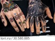 Примеры работ мастера нанесения татуировки на искусственных руках, которые лежат на стенде на Московском фестивале татуировки в Москве, Россия (2019 год). Редакционное фото, фотограф Николай Винокуров / Фотобанк Лори