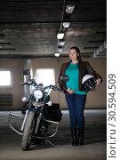 Портрет беременной женщины, стоящей рядом с мотоциклом с белым шлемом в руке, подземный паркинг. Стоковое фото, фотограф Кекяляйнен Андрей / Фотобанк Лори