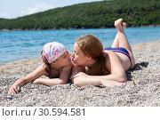 Купить «Мама с дочерью загорают на пляже, лежа на гальке. Мама целует ребенка», фото № 30594581, снято 3 июня 2016 г. (c) Кекяляйнен Андрей / Фотобанк Лори