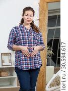 Купить «Молодая красивая беременная женщина стоит возле зеркала дома, руки в форме сердечка на животе», фото № 30594617, снято 17 февраля 2019 г. (c) Кекяляйнен Андрей / Фотобанк Лори