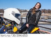 Купить «Happy and smiling young woman motorcyclist sitting on back of motorcycle, passenger of rider, white helmet on a foreground», фото № 30594653, снято 6 апреля 2019 г. (c) Кекяляйнен Андрей / Фотобанк Лори