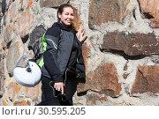 Портрет женщины мотоциклистки, стоящей возле каменной стены в экипировке, с рюкзаком на спине и прикрепленным к нему шлемом. Стоковое фото, фотограф Кекяляйнен Андрей / Фотобанк Лори
