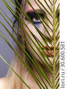 Купить «Female portrait with palm branch leaves on foreground and beauty face makeup.», фото № 30600581, снято 4 марта 2019 г. (c) Serg Zastavkin / Фотобанк Лори