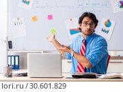 Купить «Young male financial manager working in the office», фото № 30601829, снято 11 октября 2018 г. (c) Elnur / Фотобанк Лори