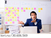 Купить «Young handsome employee in front of whiteboard with to-do list», фото № 30606569, снято 16 октября 2018 г. (c) Elnur / Фотобанк Лори