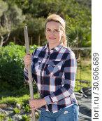 Купить «Female supervising growth of legume plants in garden», фото № 30606689, снято 20 июня 2019 г. (c) Яков Филимонов / Фотобанк Лори