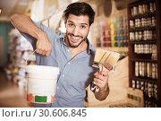 Купить «Man standing amongst racks in paint store with brushes and paint», фото № 30606845, снято 13 сентября 2017 г. (c) Яков Филимонов / Фотобанк Лори