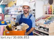 Купить «Smiling master standing near basket with tools», фото № 30606853, снято 13 сентября 2017 г. (c) Яков Филимонов / Фотобанк Лори