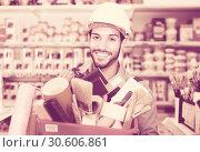 Купить «Positive guy builder holding basket with tools», фото № 30606861, снято 13 сентября 2017 г. (c) Яков Филимонов / Фотобанк Лори