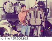 Купить «Man is demonstrating new jacket for motorbike in the store.», фото № 30606953, снято 1 сентября 2017 г. (c) Яков Филимонов / Фотобанк Лори