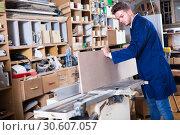 Young male carpenter adjusting chipboard indoors. Стоковое фото, фотограф Яков Филимонов / Фотобанк Лори