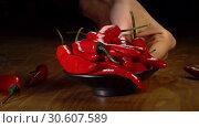 Купить «Slow motion of dropping hot chili pepper pods», видеоролик № 30607589, снято 18 апреля 2019 г. (c) Gennadiy Poznyakov / Фотобанк Лори